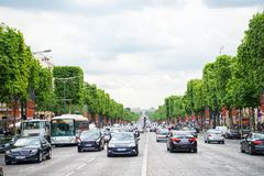 Avenue Elysian Fields with street traffic and green trees. Paris, France - June 02, 2017: avenue Elysian Fields with street traffic and green trees on cloudy sky royalty free stock photography