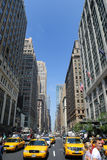 Avenue in New York City. The Avenue of Americas in New York City, lined with numerous corporate and historic buildings, as well as pedestrians and taxi cabs. May Stock Photo