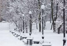 Avenue with a row of lanterns and benches during strong wind and snowstorm at winter in Moscow, Russia. Scenic view of a stock photography