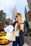 Aveny NY för telefon för blond flicka shopaholic talande femte Arkivbild