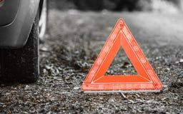 Avería del coche Muestra amonestadora roja del triángulo en el camino Fotos de archivo libres de regalías