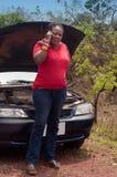 Avería del coche - llamada afroamericana de la mujer para la ayuda, ayuda del camino. Foto de archivo libre de regalías
