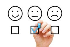 Average Customer Feedback Survey Concept. Client leaving average rating with blue marker on customer feedback evaluation form. Drawn faces survey concept stock photos
