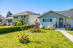 Average family house with black tulips on the yard. Average family house with black tulips on the front yard. Residential house on sunny day in Canada stock photography