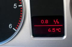Average fuel consumption and a thermometer in used family car dashboard . Average fuel consumption and a thermometer in used family car dashboard close up shot Royalty Free Stock Images