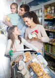 Parents with two little kids holding purchases in store Royalty Free Stock Photo