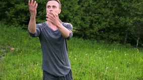 An average plan a young man in Indian clothes and pants Aladdin practices qigong while doing exercises while working. With qi energy. outdoors in summer next to stock video footage