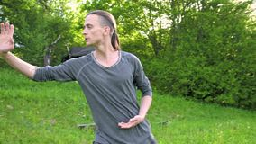 An average plan a young man in Indian clothes and pants Aladdin practices qigong while doing exercises while working. With qi energy. outdoors in summer next to stock video