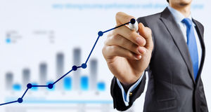 Average sales report. Close view of businessman drawing on screen market infographs Stock Image
