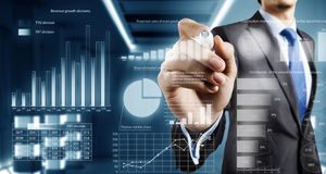 Average sales report. Close view of businessman drawing on screen market infographs Royalty Free Stock Photos