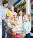 Satisfaction parents with two kids holding purchases in store. Average satisfaction parents with two kids holding purchases in store Stock Image