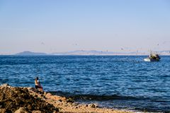 Fishing Boat Sailing On The Horizon Stock Photography