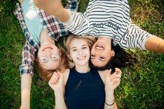 Avere migliore tempo con gli amici gruppo di studenti che si trovano sul godere dell'erba Fotografie Stock Libere da Diritti