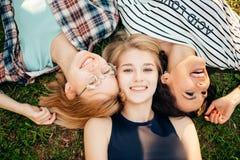 Avere migliore tempo con gli amici gruppo di studenti che si trovano sul godere dell'erba Fotografia Stock