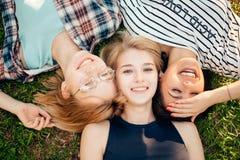 Avere migliore tempo con gli amici gruppo di studenti che si trovano sul godere dell'erba Fotografie Stock