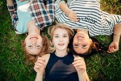 Avere migliore tempo con gli amici gruppo di studenti che si trovano sul godere dell'erba Immagine Stock