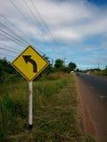 Avertissement gauche de signe de courbe sur la route Image libre de droits
