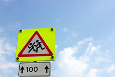 Avertissez le panneau routier d'enfants dans le cadre jaune au-dessus de lumineux Image stock