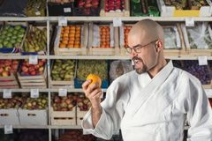AVery hungry man against the background with racks with fruits and vegetables dressed in Japanese kimono and hakama Stock Photography