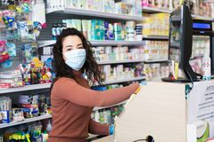 Avetrana, Italy, - Marth, 13, 2020. Beautiful young cashier with medical mask and gloves working at the supermarket. Respecting