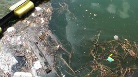 Avfall och avskräde som svävar på yttersidan av vattnet Vattenförorening med smutsig och plast- avskräde som svävar på havet arkivfilmer