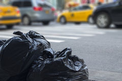 Avfallpåsar med oskarp trafik i bakgrund i stads- environmen royaltyfri bild
