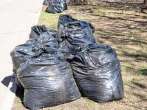 Avfallpåsar som fylls med kull på gräsmatta längs vägen royaltyfri foto