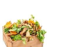 Avfalls för grönsakkökmat i en beträffande använd träbehållare för hemmet som composting vit bacground arkivbild