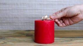 Avfyra en röd stearinljus för vax med en match arkivfilmer