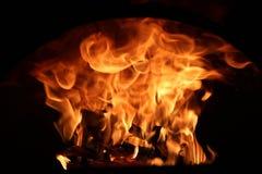 Avfyra i spisen på en mörk bakgrund arkivbild