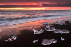 Avfyra jokulsarlonsoluppgång på stranden i Island Royaltyfri Foto