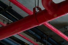 Avfyra sprinkleranläggningen med röda rör som hänger från tak inom byggnad Branddämpning Brandskydd och avkännare arkivbild