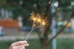 Avfyra trefaldigt bengali ljus i hand med suddig bakgroundnärbildsikt arkivfoton
