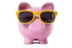 Avgångbesparing, lopppengarbegrepp, Piggybank bärande solglasögon Royaltyfria Bilder