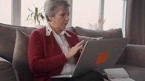 Avgångkvinna som ser hennes moderna cell- och bärbar dator arkivfilmer