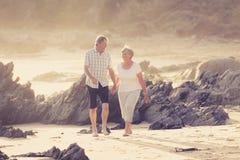 Avgick mogna par för älskvärd pensionär på deras 60-tal eller 70-tal att gå som var lyckligt och som var avkopplat på strandhavsk Arkivbild