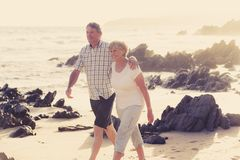 Avgick mogna par för älskvärd pensionär på deras 60-tal eller 70-tal att gå som var lyckligt och som var avkopplat på strandhavsk Royaltyfri Bild