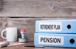Avgångplan och pension Två limbindningar på skrivbordet i kontoret Arkivfoto