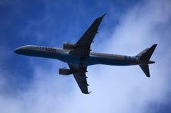 Avião comercial azul e branco que voa à esquerda na baixa altura Fotos de Stock