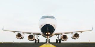 Avião comercial branco que está na pista de decolagem do aeroporto no por do sol A vista dianteira do avião do passageiro está de Fotografia de Stock Royalty Free