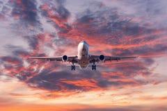 Avi?o de aterrissagem do passageiro no por do sol colorido fotos de stock