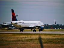 Avião de Delta Airlines na pista de decolagem fotografia de stock