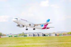 Avião de Eurowings antes de aterrar/após a decolagem, céu com nuvens Fotografia de Stock