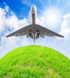 Avião de passageiros sobre um planeta verde. Foto de Stock