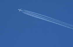 Avião de passagem com contrails imagem de stock