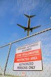 Avião de passagem e cerca de perímetro do aeroporto Fotografia de Stock Royalty Free