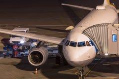 Avião do passageiro em uma porta do aiport na noite Foto de Stock