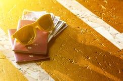 Avião do passaporte dos óculos de sol no fundo amarelo na luz solar fotos de stock