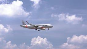 Avião do voo pacífico da linha aérea de Jetstar através do céu das nuvens para preparar-se à aterrissagem filme