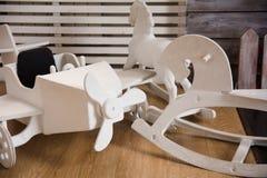 Avião e cavalos de madeira do brinquedo no assoalho Imagem de Stock